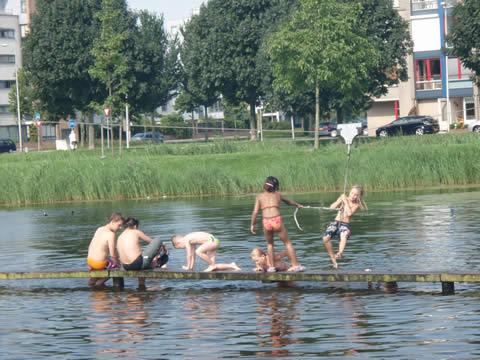 kinderen spelen op een vijvervlonder